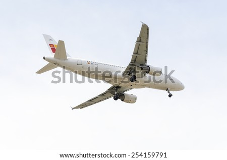 MADRID, SPAIN - FEBRUARY 14th 2015: Airplane -Airbus A320-, of -Iberia- airline, landing on Madrid-Barajas -Adolfo Suarez- airport, on February 14th 2015. - stock photo