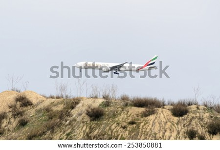 MADRID, SPAIN - FEBRUARY 14th 2015: Airplane -Boeing 777-300ER-, of -Emirates- airline, landing on Madrid-Barajas -Adolfo Suarez- airport, on February 14th 2015. - stock photo