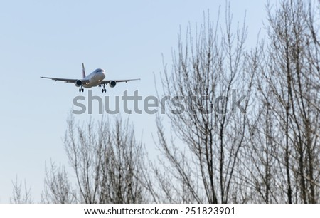 MADRID, SPAIN - FEBRUARY 08th 2015: An airplane -Airbus A320-, of the -Iberia- airline, landing on Madrid-Barajas airport, on February 8th 2015. - stock photo