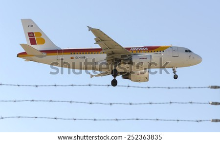 MADRID, SPAIN - FEBRUARY 08th 2015: An airplane -Airbus A319-, of the -Iberia- airline, landing on Madrid-Barajas airport, on February 8th 2015. - stock photo