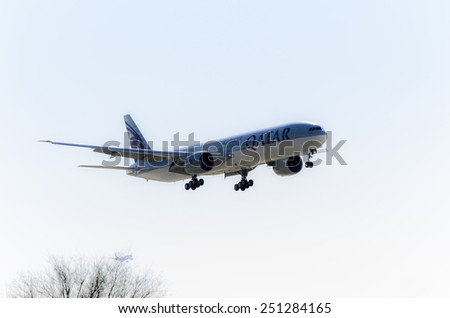 MADRID, SPAIN - FEBRUARY 08th 2015: An airplane -Boeing 777-300ER-, of the -Qatar- airline, landing on Madrid-Barajas airport, on February 8th 2015. - stock photo
