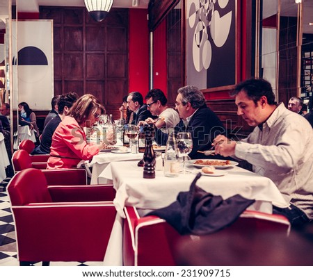 MADRID, SPAIN - MARCH 5, 2014: People eating at small cafe in the city center of Madrid. Toned picture - stock photo