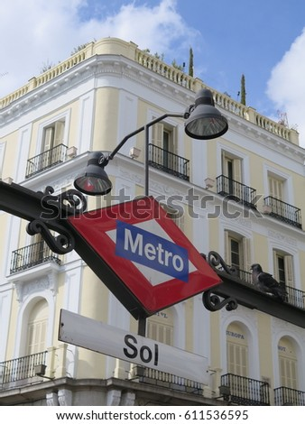 Madrid, Spain - March 2017: Sign of the metro of Madrid in Sol station and El Corte Ingles department store building in the background