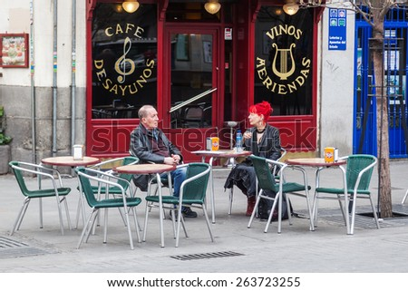 MADRID, SPAIN - MARCH 17, 2015: unidentified couple sitting in a street cafe on the Plaza Isabel II. Madrid is the capital and largest city of Spain and the third largest city on the European Union. - stock photo