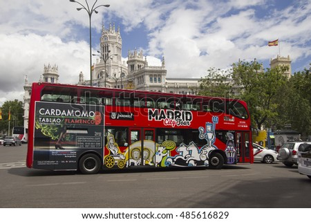 Madrid, Spain - May 29, 2016: City Tour bus with tourists drives across Cybele Plaza and the communications palace in Madrid, Spain on May 29, 2016