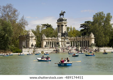 Madrid, Spain - May 29, 2016: People boating in the pond of El Retiro park in front of the monument for king Alfonso in Madrid, Spain on May 29, 2016