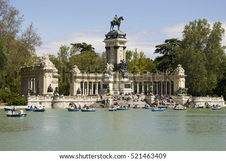Madrid, Spain - May 29, 2016: People boating in the pond of El Retiro park in front of the monument for king Alfonso XII in Madrid, Spain on May 29, 2016