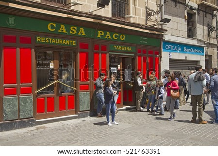 Madrid, Spain - May 29, 2016: People stand in front of a restaurant and bar in the historical part of Madrid, Spain on May 29, 2016