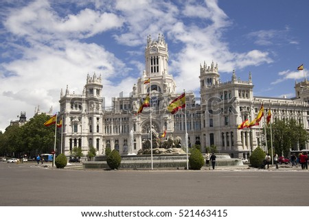 Madrid, Spain - May 29, 2016: People stand near the fountain with Spanish flags in front of the palace of Telecommuncation on Plaza Cybeles in Madrid, Spain on May 29, 2016