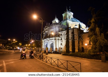 Madrid, Spain - May 6, 2012:  Side view of the Real Basilica de San Francisco el Grande on a sunny spring night and moped bikers on street, Madrid, Spain