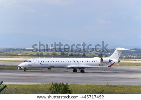 MADRID, SPAIN - MAY 15th 2016: Aircraft -Bombardier CRJ-900- of -Air Nostrum- airline, direction to airport terminal of Madrid-Barajas -Adolfo Suarez- airport, after it has landed, on May 15th 2016. - stock photo