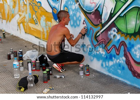 MADRID, SPAIN-SEPT. 18:Unidentified man draws on the wall with a can of spray during first International Graffiti and Dance on September 18, 2012 in Madrid, Spain.