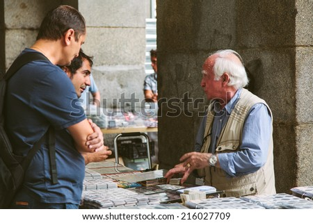 MADRID, SPAIN - SEPTEMBER 7: People at the Collectible Market of Stamps and Coins in Plaza Mayor, one of the most traditional Madrid classics on September 7, 2014 in Madrid. - stock photo