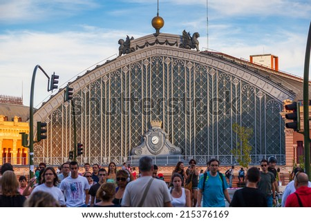 MADRID, SPAIN - SEPTEMBER 4: People Walking Besides the Atocha Railway Station, the largest and primary station serving commuter, intercity and regional trains, on September 4, 2014 in Madrid, Spain - stock photo