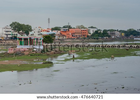 Madurai, India - October 19, 2013: Broad view on shallow Vaigai river with empty Meenakshi shrine and pedestrian bridge. Horses and people in the photo.
