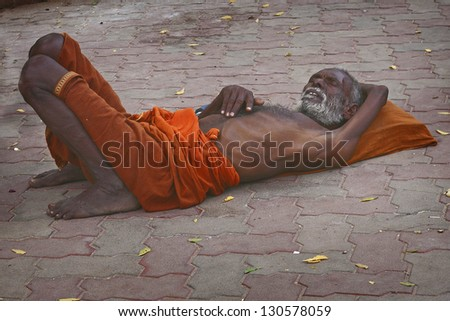 MADURAI, TAMILNADU, IND-JAN 6: A Sadhu sleeping at  Meenakshi Temple in Madurai, Tamil Nadu, India, on January 6, 2013. The two sectarian divisions in sadhu community are Shaiva and Vaishnava sadhus. - stock photo