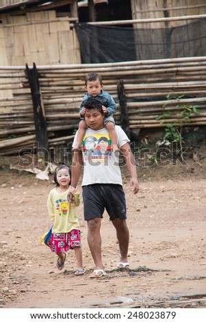 Mae Hong Son, Thailand - August 22, 2013: A Burmese refugee father taking his child back from school in the evening in Ban Mae Surin temporary shelter in Mae Hong Son, Thailand - stock photo