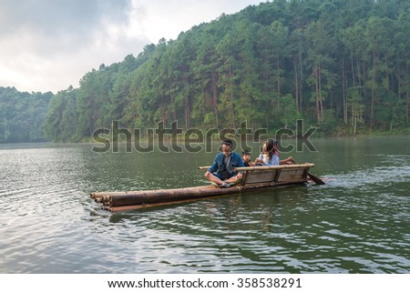 Mae Hong Son, Thailand DEC 30 2015:Tourists get on a Bamboo raft for sightseeing around to Pang Ung reservoir lake view beautiful mountain scenes, and hazy fog in the morning.