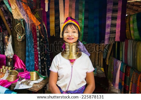 MAE HONG SON, THAILAND - DEC 4, 2013: Unidentified Karen (Kayan Lahwi Padaung) Long Neck woman with traditional brass coils selling hand made textile in tribe village. Chang Mai province, Thailand - stock photo