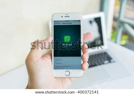 MAE HONG SON, THAILAND - MARCH 13, 2016: Man try to use social Internet service WhatsApp screen on blue background. iPhone 6S was created and developed by the Apple inc. - stock photo