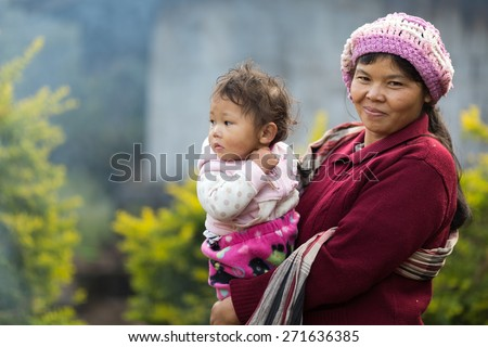 MAE KLANG LUANG, THAILAND, DECEMBER 31, 2014: A Karen tribe woman in traditional clothes with her kid in the village of Mae Klang Luang in the Doi Inthanon national park near Chiang Mai, Thailand - stock photo