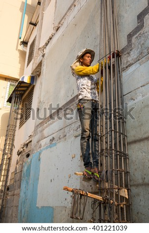 MAE SOT, TAK, THAILAND - APRIL 05 : Unidentified Myanmar migrant worker in construction  commercial building site climbing on a metal pole at Mae Sot, Tak, Thailand on APRIL 05 ,2016.