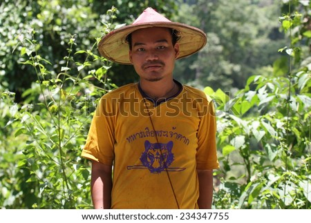 MAE SOT, THAILAND - SEPTEMBER 1: A typical hill tribe man wearing a coolie hat beside the road near Mae Sot, Thailand on the 1st September, 2014.