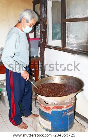 MAEHONGSON, THAILAND - NOVEMBER 16,2014 : Barista traditional coffee beans roasting in metal basin at Mae hong son, Thailand