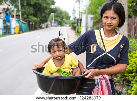 MAESOT, THAILAND - JULY5 : Unidentified migrant Myanmar worker is bring her baby into a plastic container to take to the street at Mae Sot, Tak, Thailand on JULY5, 2015