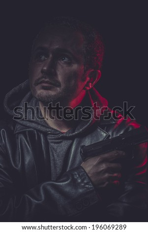 Mafia Assassin, man with black coat and gun - stock photo