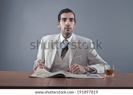 Mafia fashion man wearing white striped suit and tie. Sitting at table with glass of whisky and newspaper. Studio shot.