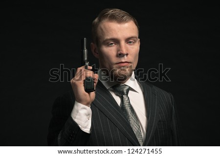 Mafia man in suit with cocaine and gun. Studio shot. - stock photo