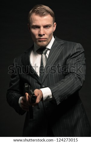 Mafia man in suit with cocaine and rifle. Studio shot. - stock photo