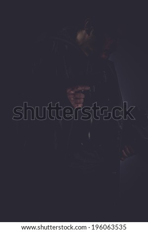 mafia, portrait of stylish man with long leather jacket, gun armed - stock photo