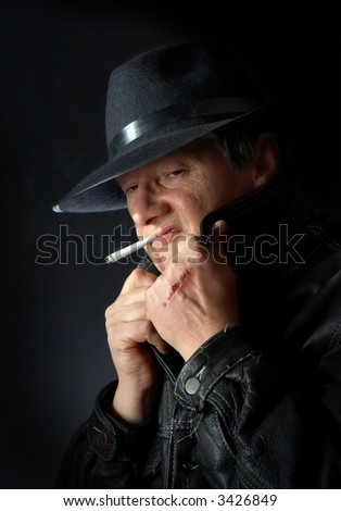 Mafia type with scar on his hand, smoking a cigarette - stock photo