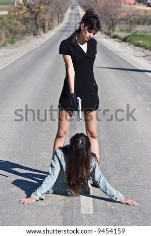 Mafia woman aiming to another in the middle of nowhere - stock photo