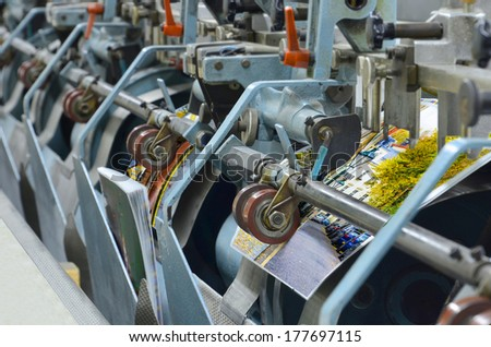 magazine binding process after offset print. Close-up of the conveying process of a full-automatic binding perfect bound units. - stock photo