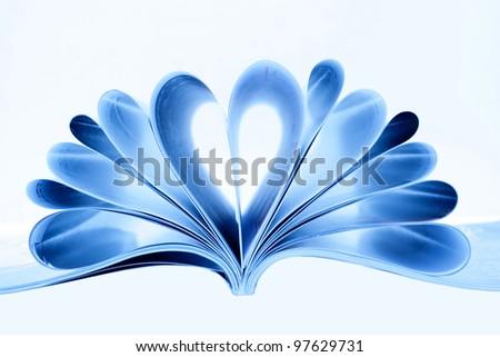 Magazine folded to heart shape isolated on white - stock photo