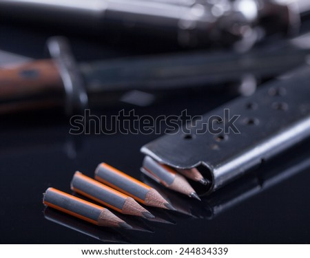 magazine knife, pen in the form of bullet and blurred gun and in the background - stock photo