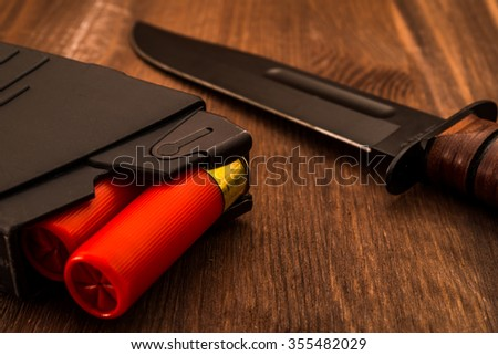 Magazine with red cartridges 12 gauge and combat knife on the wooden table. Close up view - stock photo