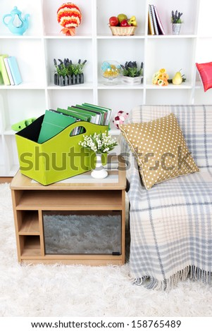 Magazines and folders in green box on bedside table in room - stock photo