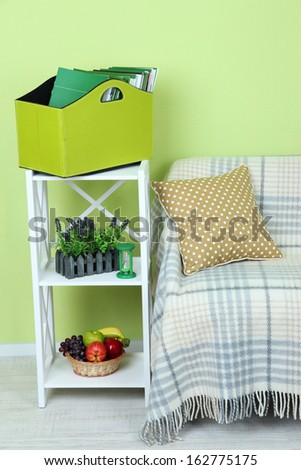 Magazines and folders in green box on shelf in room