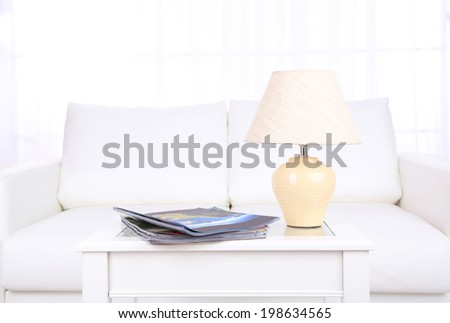 Magazines and lamp on coffee table in room