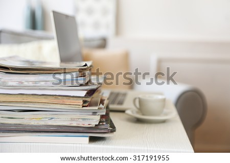 Magazines and laptop on table in living room, close up - stock photo