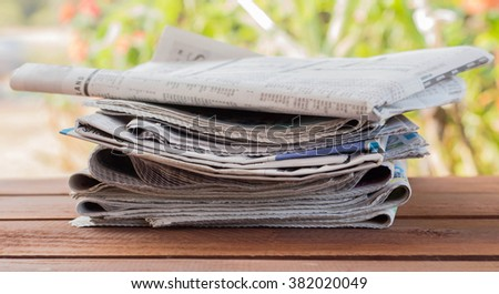 Magazines and newspapers on a wooden table. - stock photo