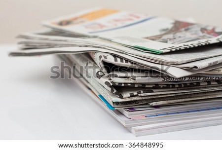 Magazines and newspapers on white table.