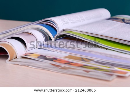 Magazines on wooden table on dark background