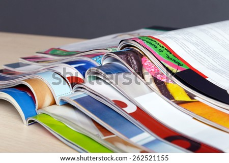 Magazines on wooden table on gray background - stock photo