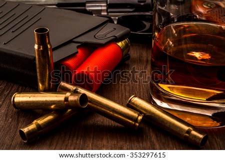 Magazines with red cartridges 12 gauge and glass of whiskey with revolver on the wooden table. Close up view - stock photo