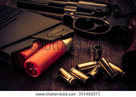 Magazines with red cartridges 12 gauge and revolver on the wooden table. Close up view, image vignetting and the yellow-blue toning - stock photo
